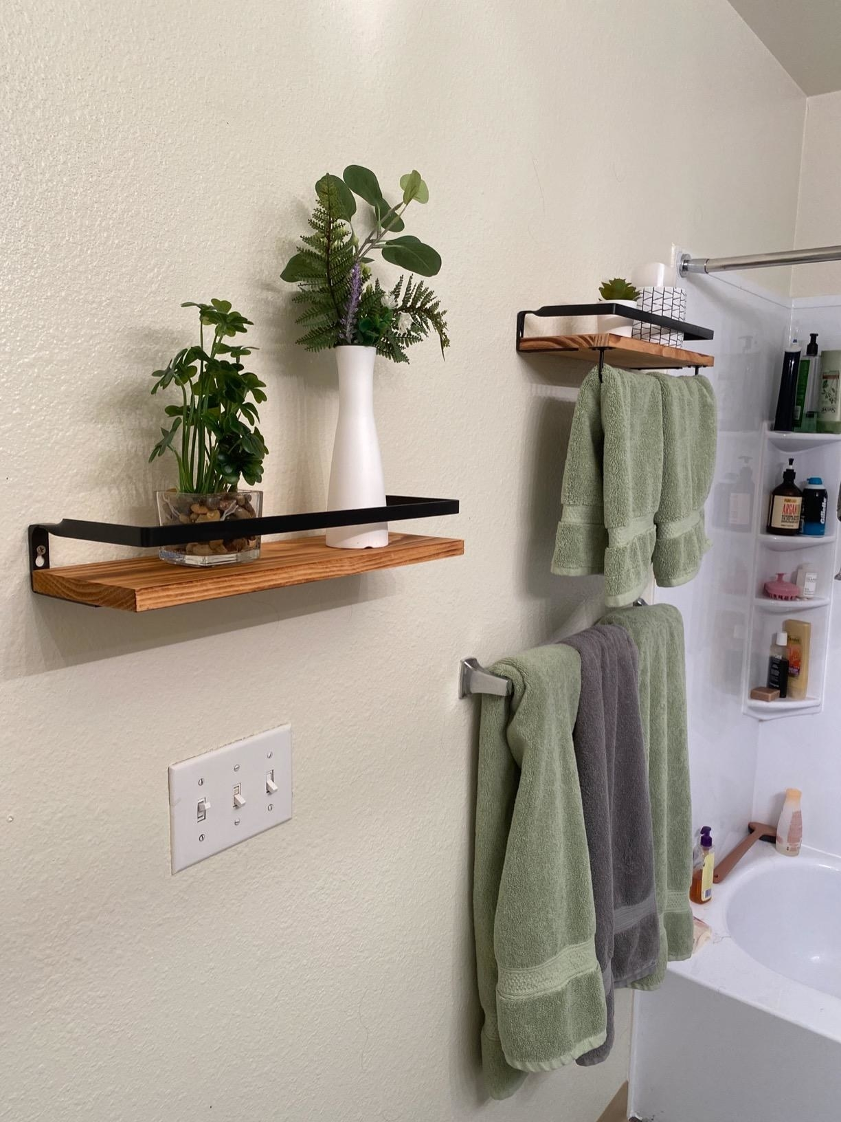 Brown floating shelves with white plant vases and green towels hanging below