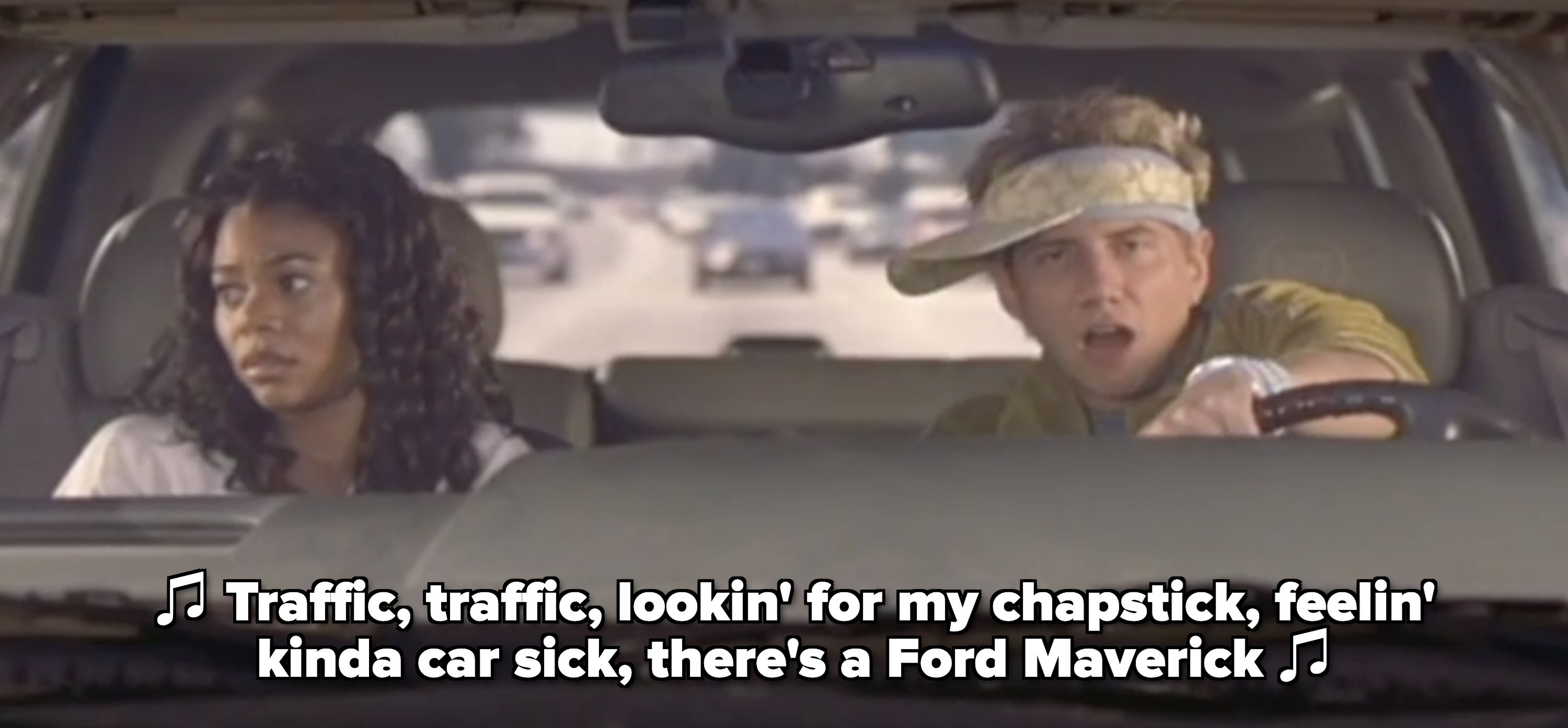 """Brad rapping in the car: """"Traffic, traffic, lookin' for my chapstick, feelin' kinda car sick, there's a Ford Maverick"""" while Shondra sits in the passenger seat, looking annoyed"""