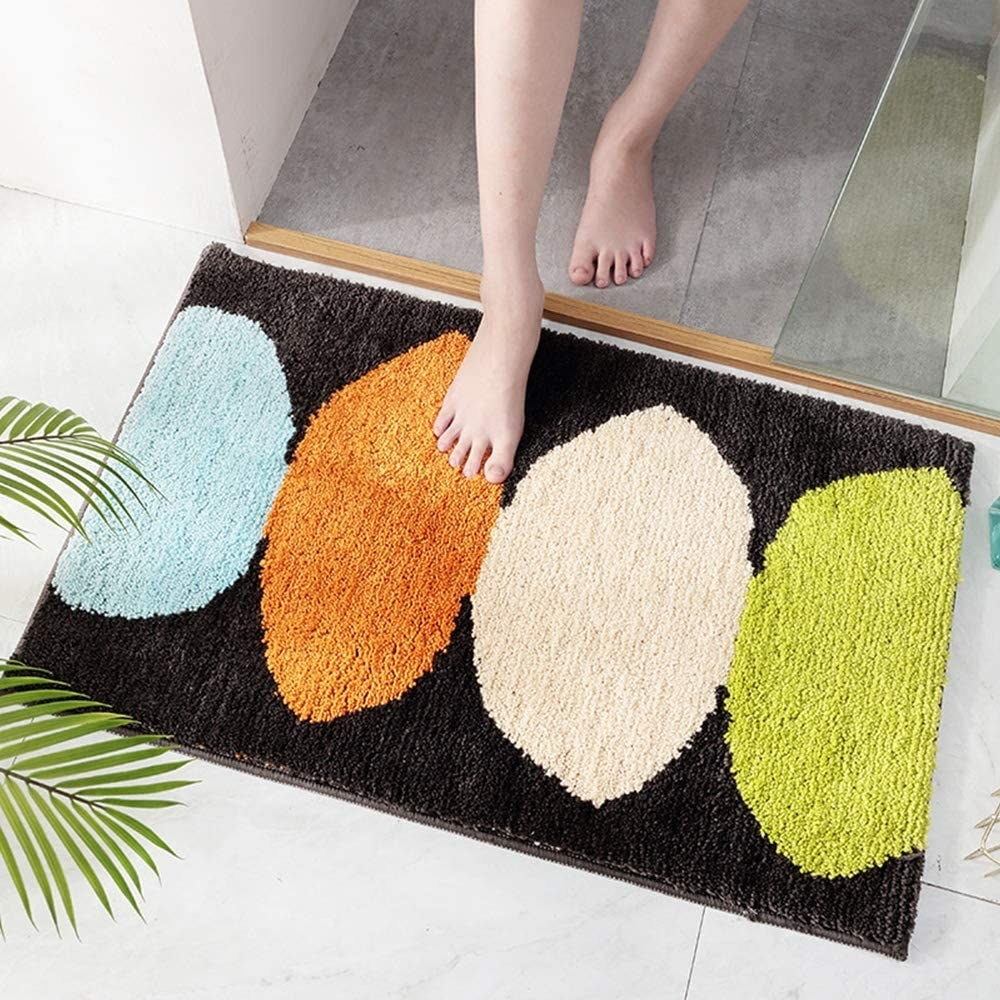 Model walks out of shower to step on blue, orange, white, and green abstract-print shaggy rug