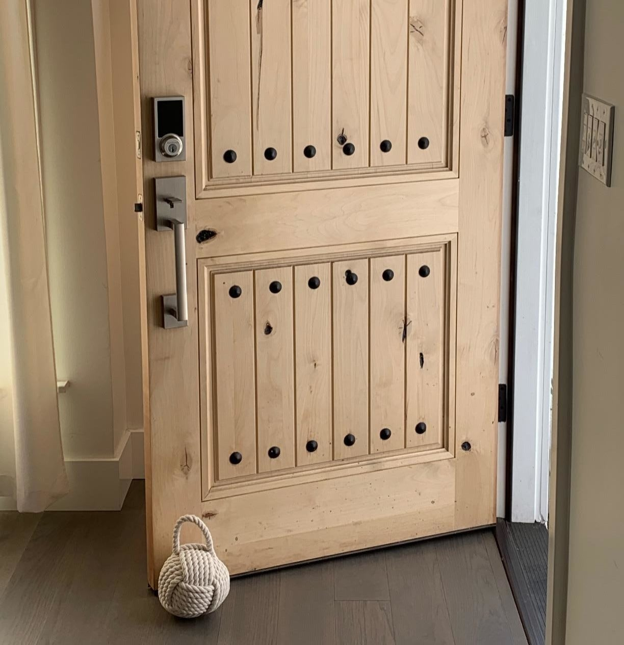reviewer image of the ivory Creative Co-Op Nautical Rope Knot Cotton Door Stop holding a customer's front door open