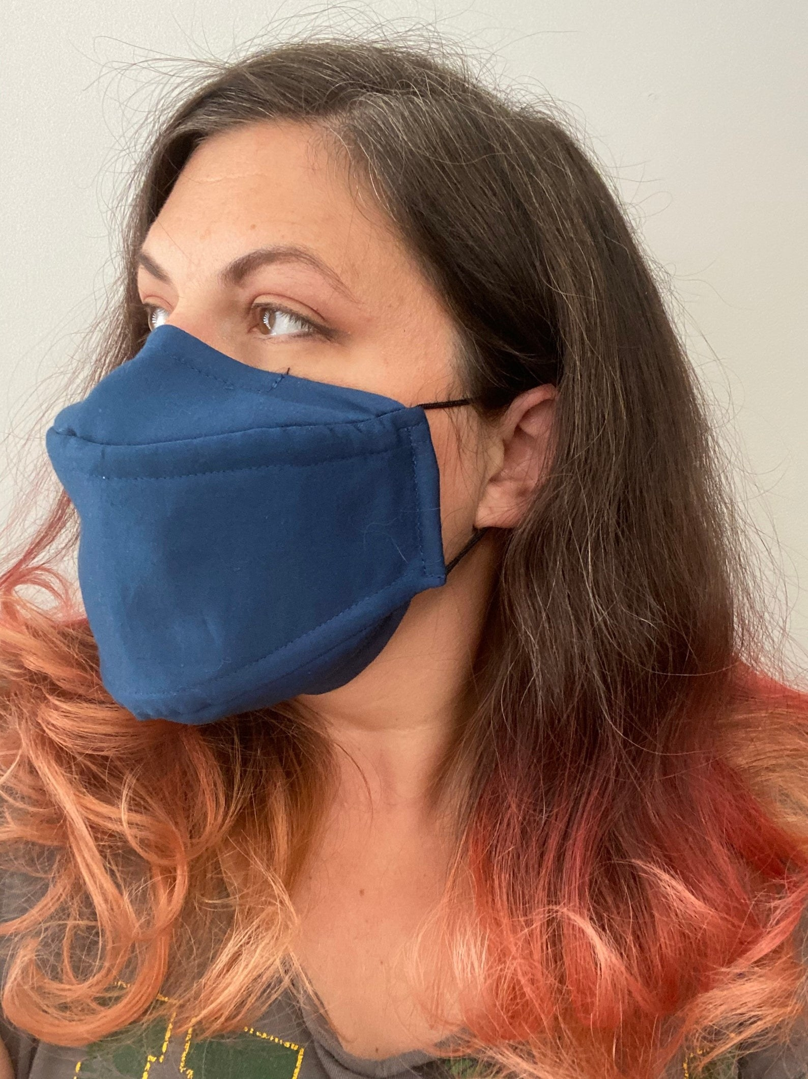 A model in a structured blue face mask that sits off the mouth and nose but still covers it
