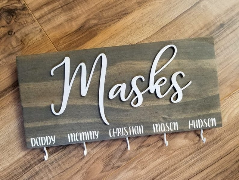 "A wooden sign that says ""Masks"" in white script with five small hooks and names above them"