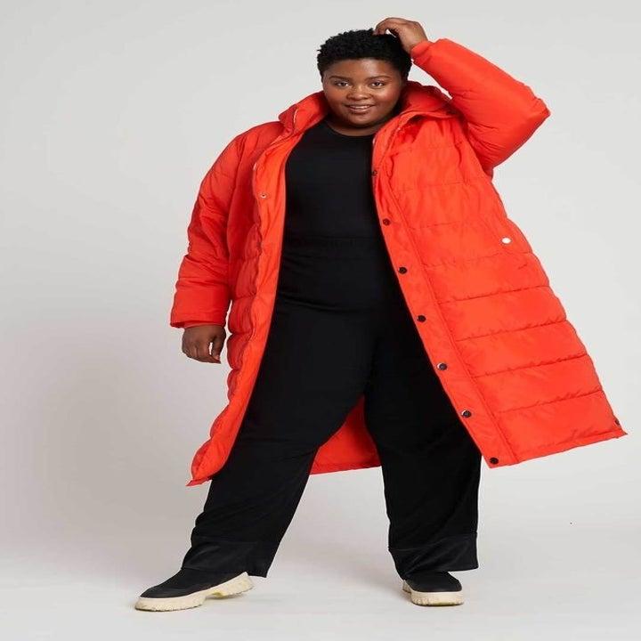 A model wearing the coat in electric orange