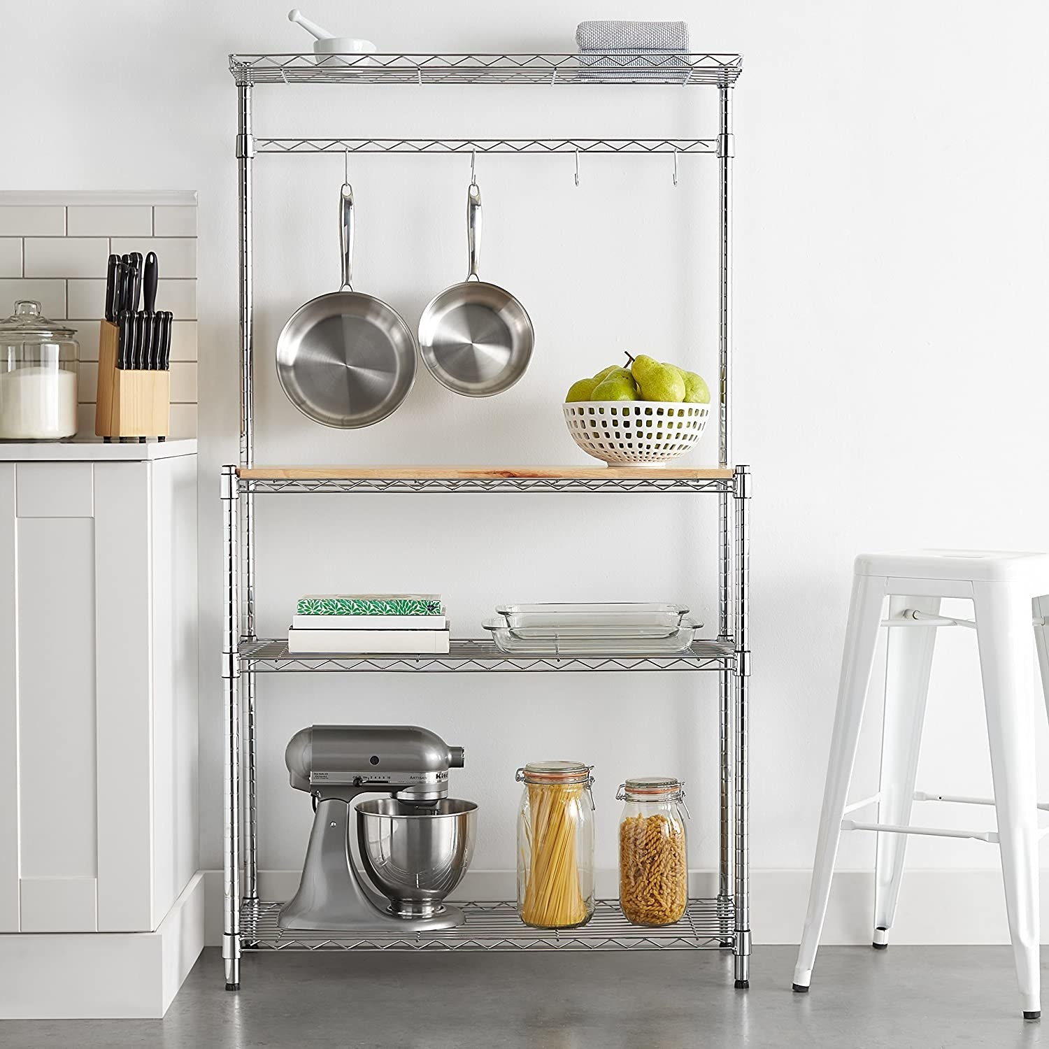 The four tier shelf holding various kitchen supplies