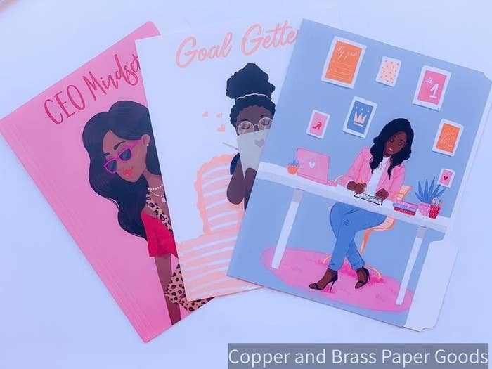 """The three folders: a pink one with a stylishly dressed woman and the text """"CEO mindset,"""" a light blue one with a woman working on a tablet in bed and the text """"goal getter,"""" and a blue one with a woman working in an adorably decorated office"""