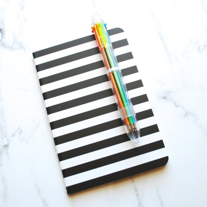 The transparent pen with colorful ink cartridges clipped to a notebook