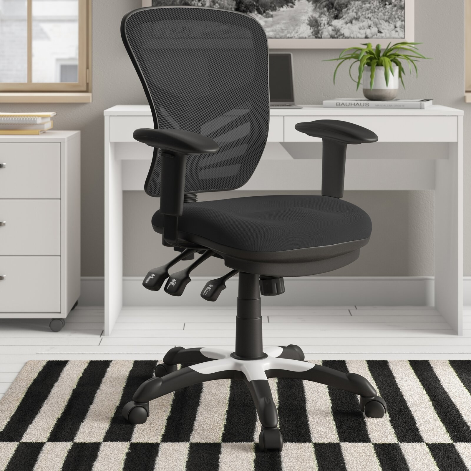 The black swivel chair with armrests and a mesh back