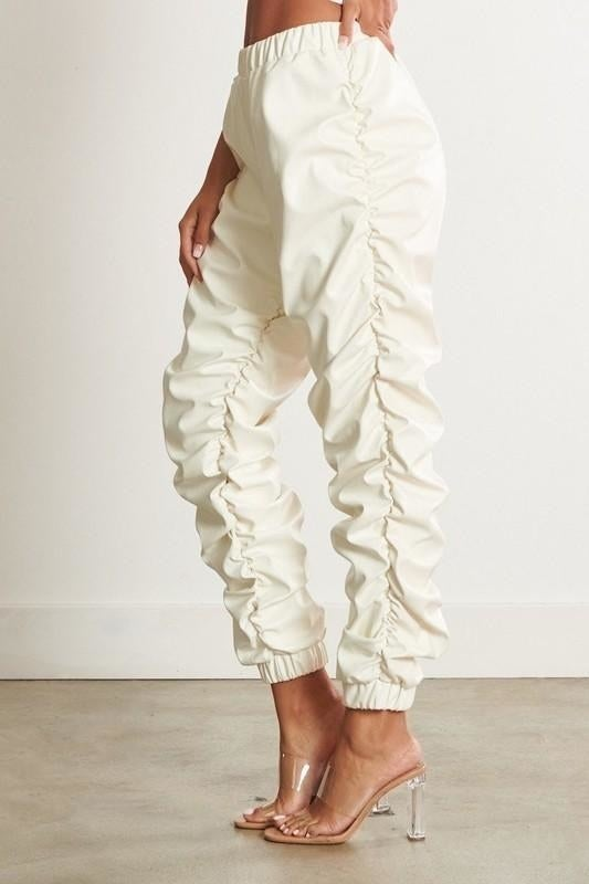 Model wearing white joggers with rouched sides