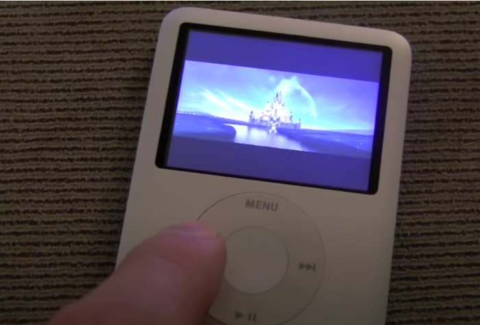 A finger pushing the button on an iPod Nano playing a Disney movie.