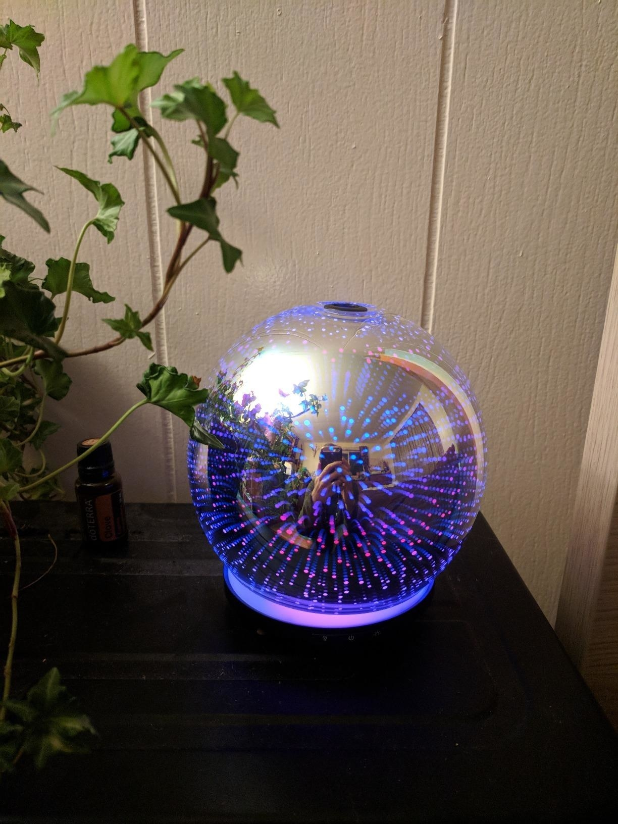 Purple, red. and blue LED galaxy-inspired diffuser on tabletop