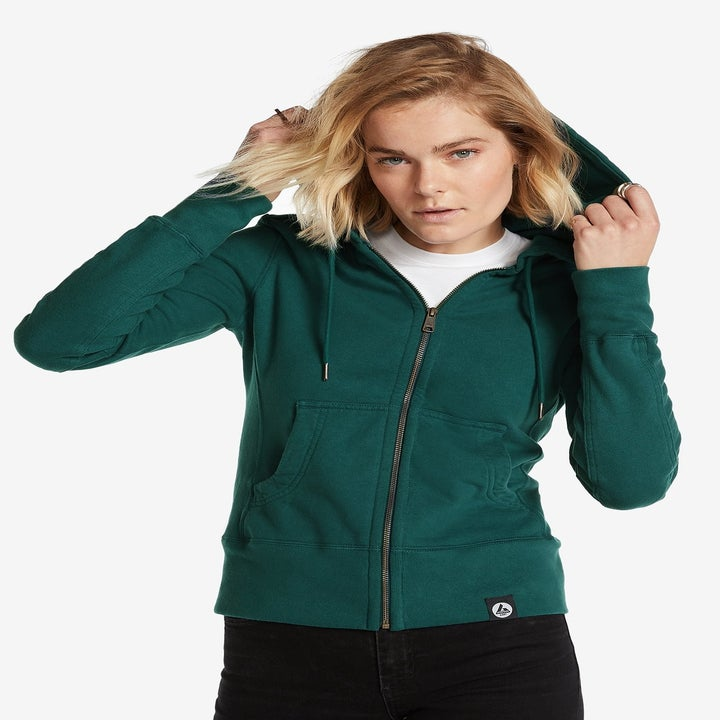 Front view of a model wearing the hoodie in blue spruce