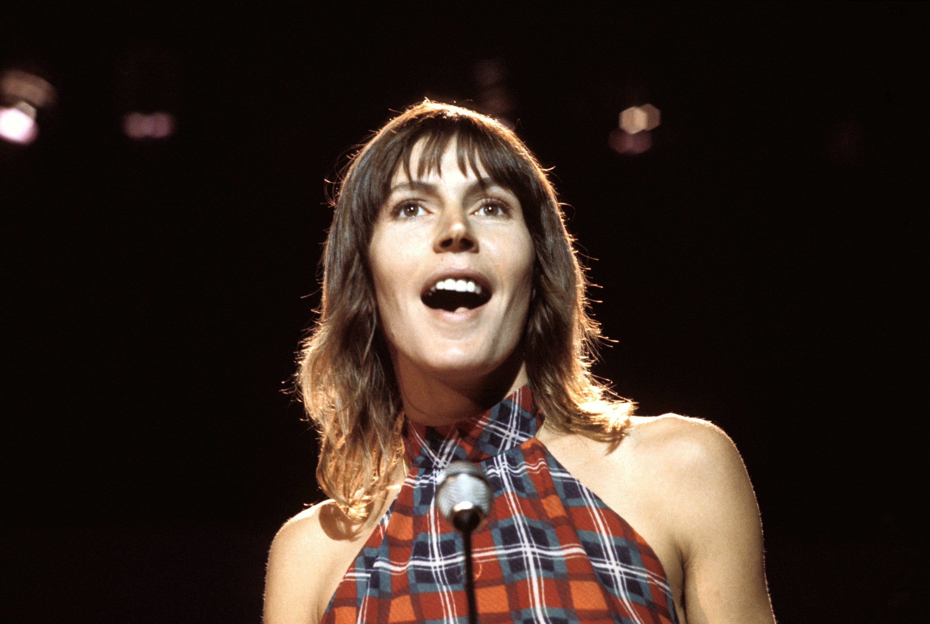 Reddy in a halter top singing on stage looking at the audience