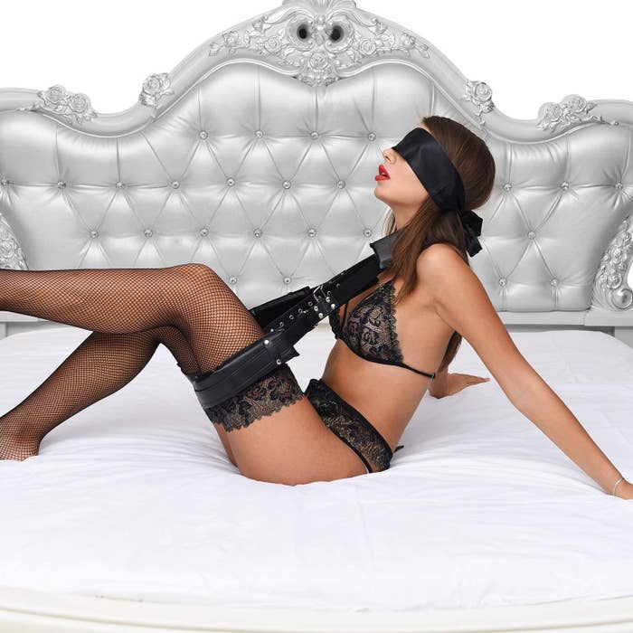 a model reclined on a bed with the utimi bondage thigh restraint sling on