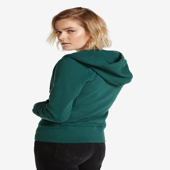 Back view of a model wearing the hoodie in blue spruce