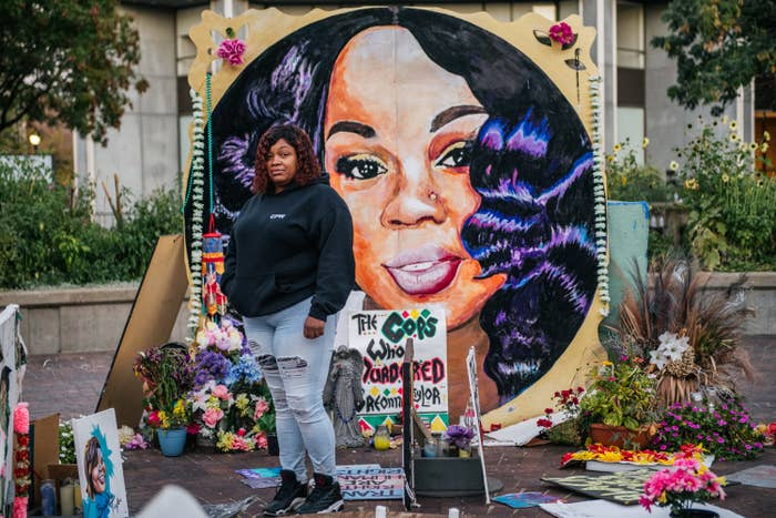 A woman standing in front of a mural of Breonna Taylors that's surrounded with flowers and tributes