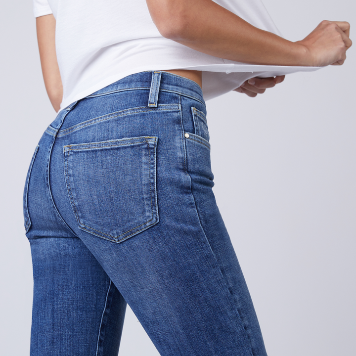 Back view of a model wearing the jeans in medium blue