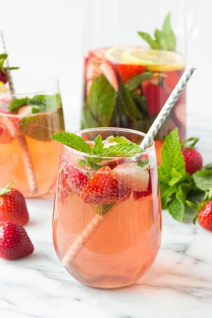 A pitcher and glasses of strawberry mint sangria.