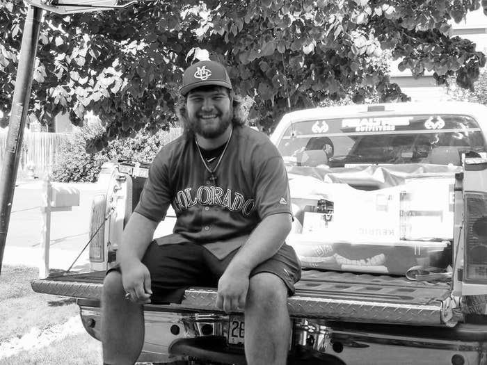 A young man sits in the bed of a pickup truck, wearing a baseball jersey and CMU cap