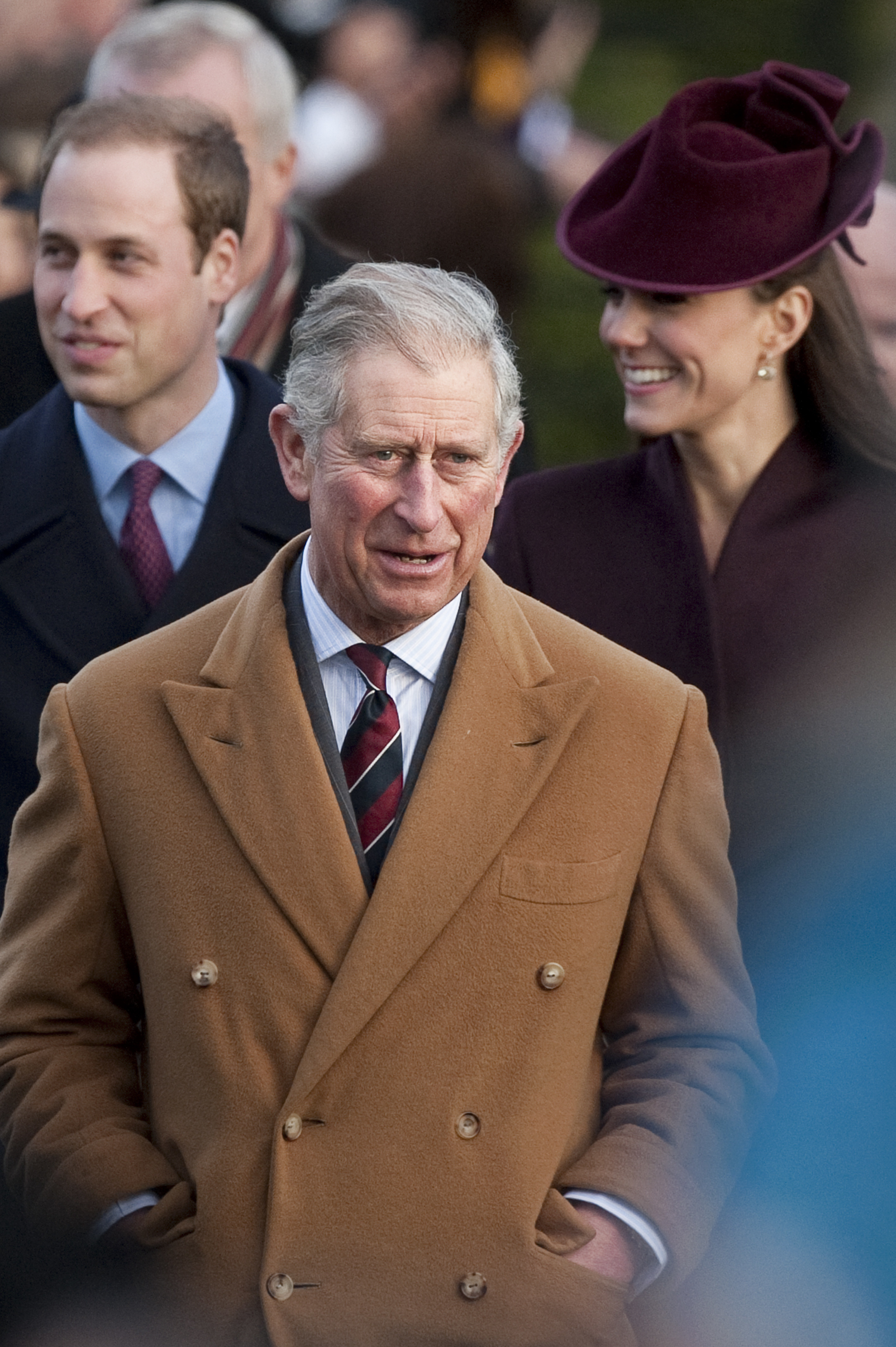 Prince Charles walking with Prince William and Duchess Kate Middleton behind him