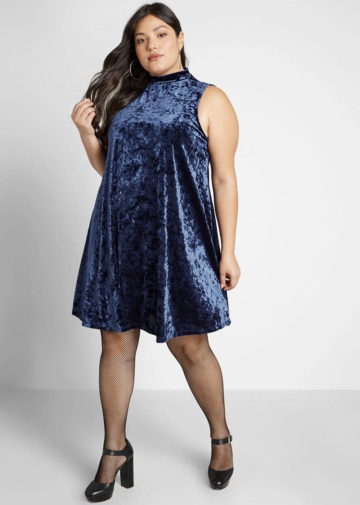 Model in a blue velvet sleeveless mock neck swing dress