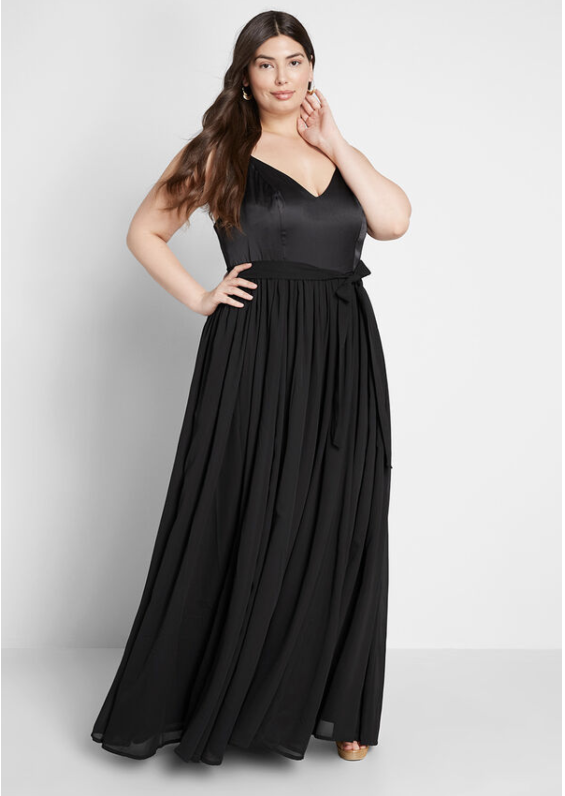 Model in black v-neck maxi dress with tulle skirt and belt that cinches at waist