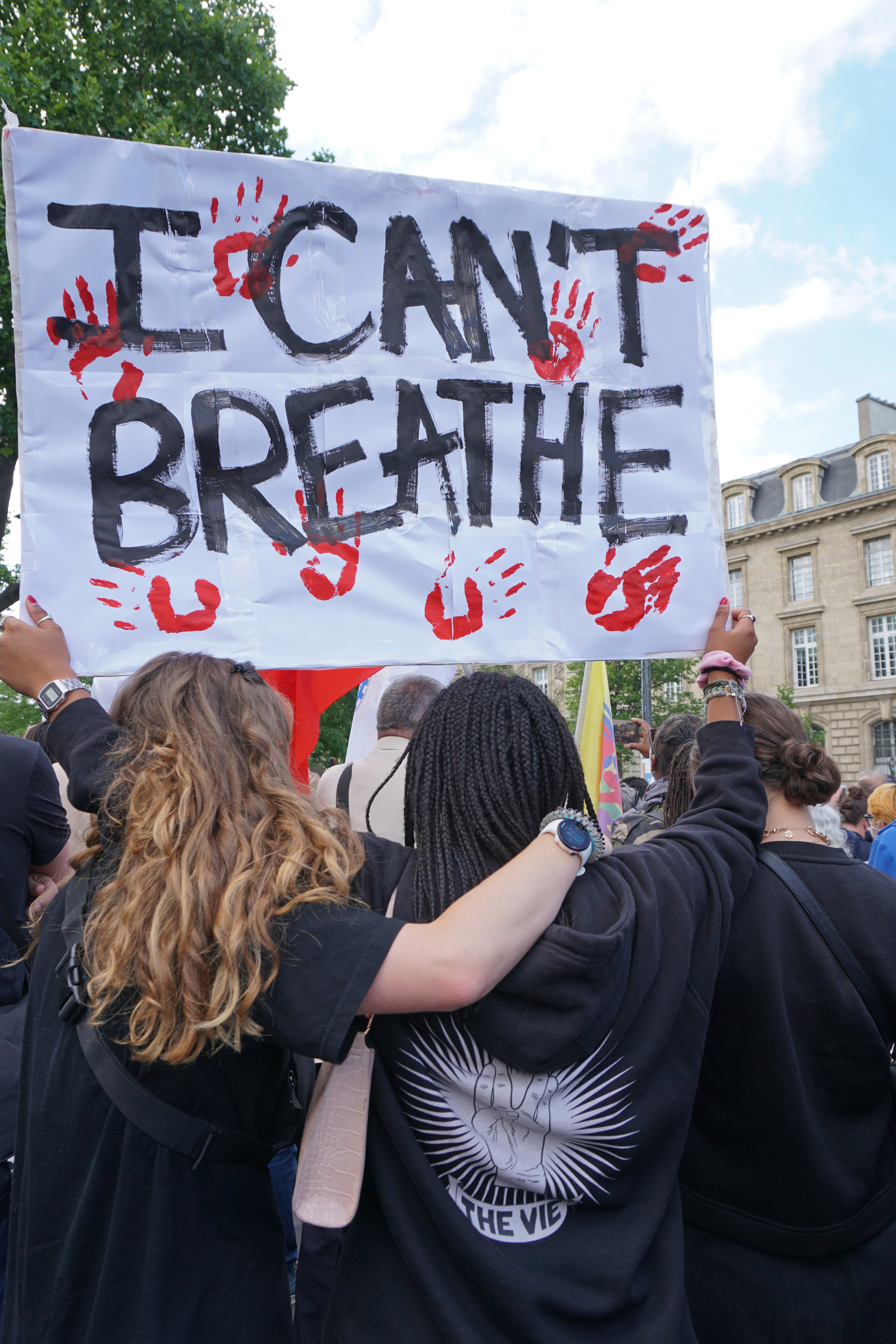 Protestors holding a posters that reads 'I can't breath' with hand prints all over it