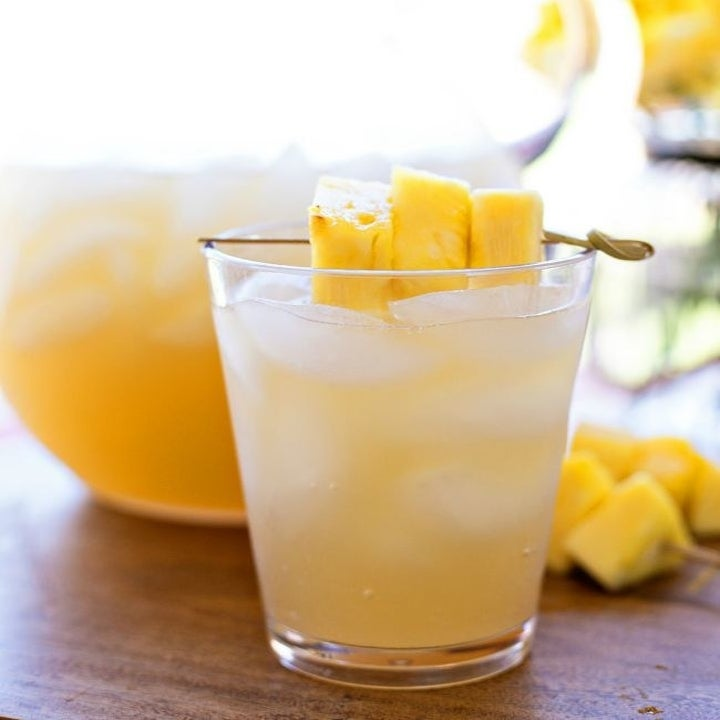 A glass of pineapple rum punch with sliced pineapples.