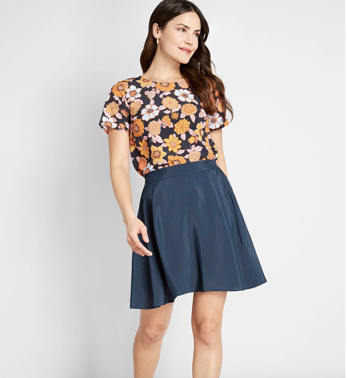 Model in navy high-waisted A-line skirt that falls above the knee