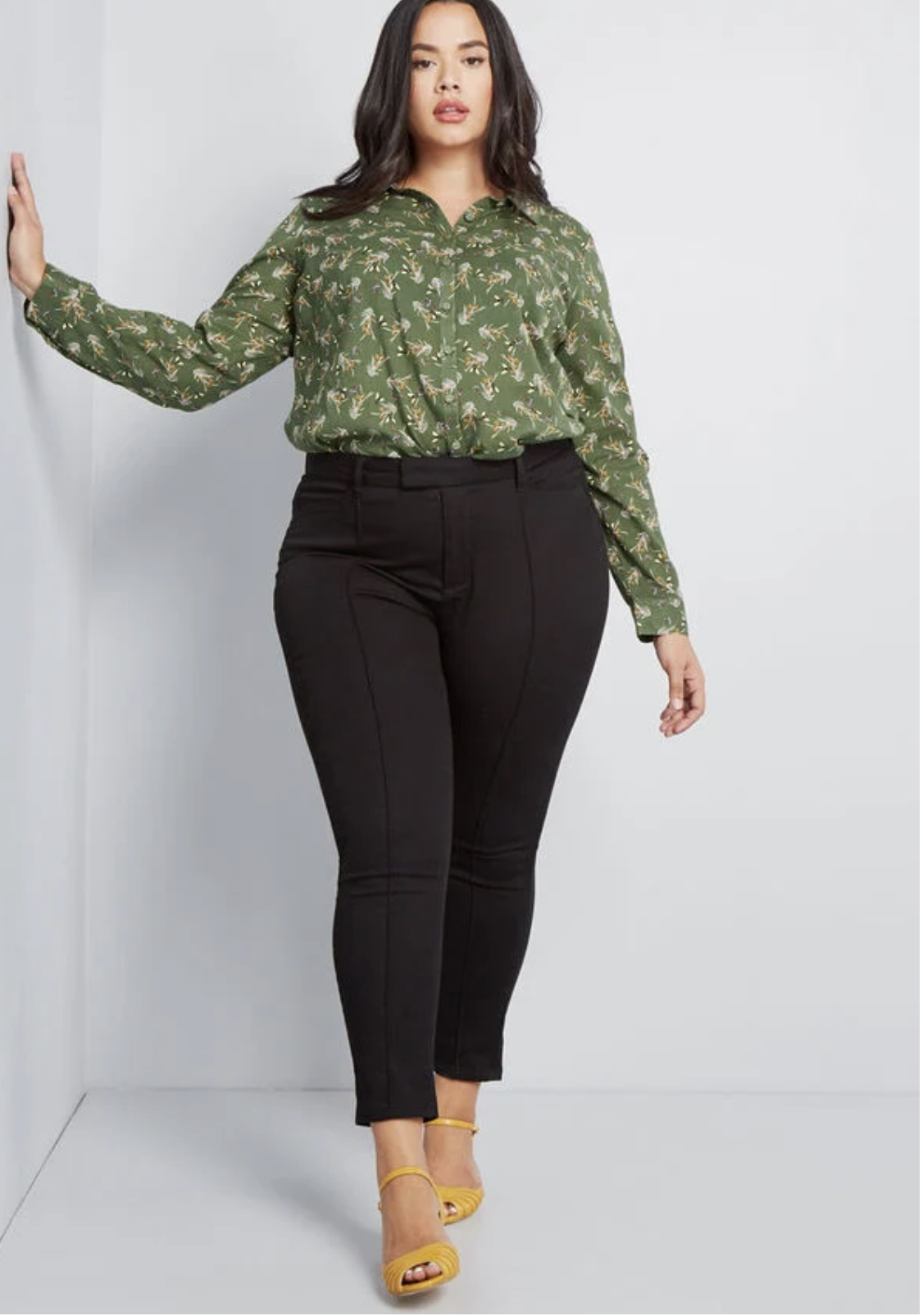 Model in a pair of black highwaisted ankle pants with a seam down the middle of each leg