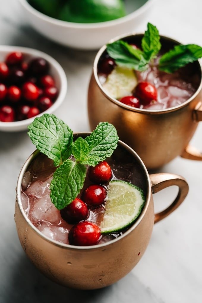 Two copper mugs filled with cranberry Moscow mules.
