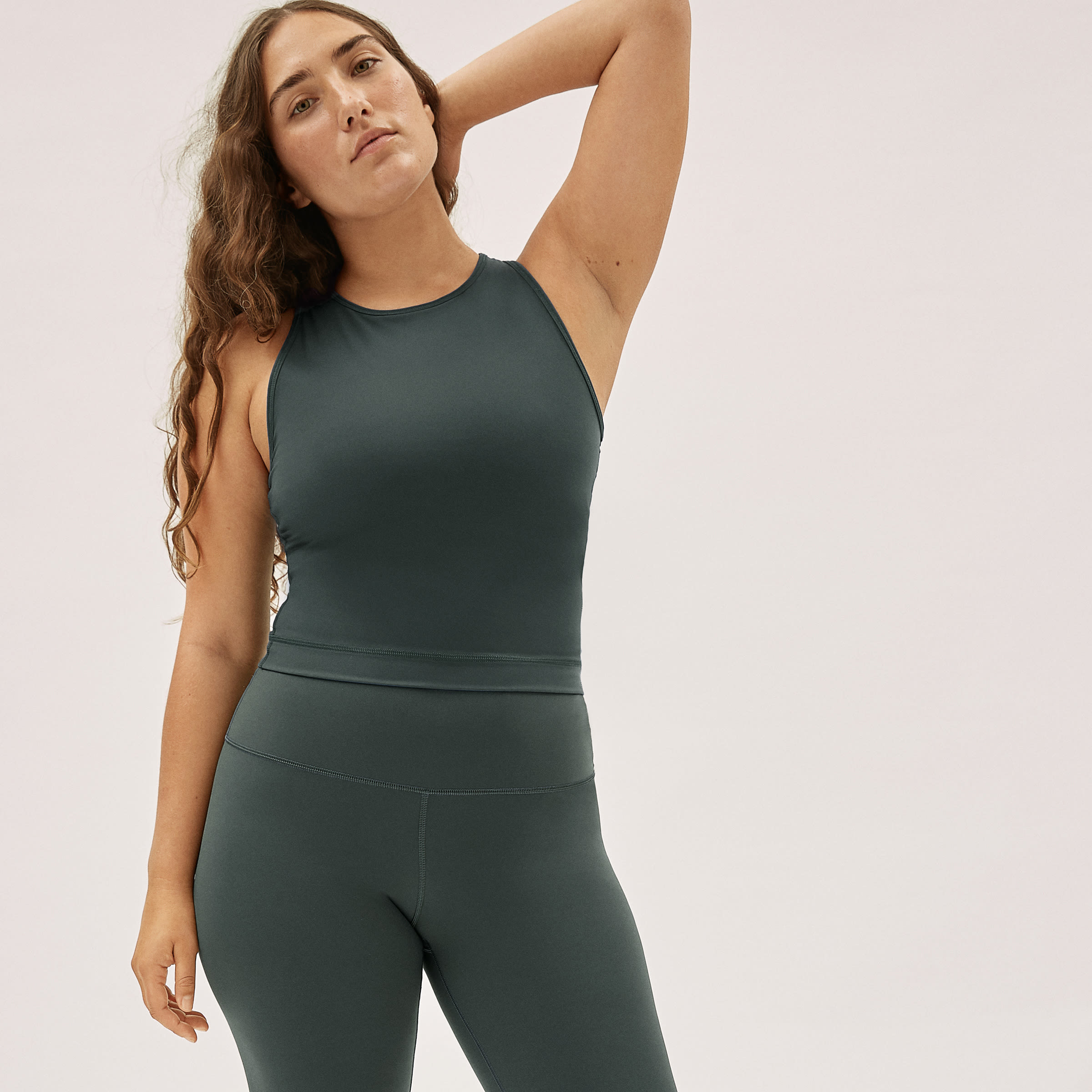 model wearing the high-neck tank in dark green