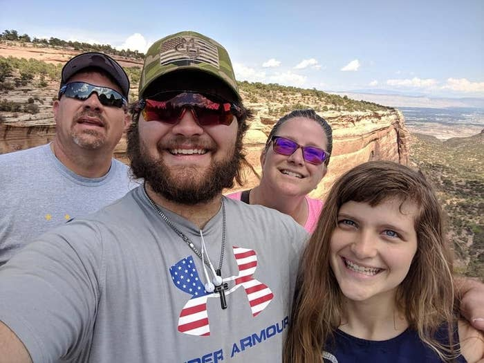A family of four stands in front of a canyon, smiling for a selfie
