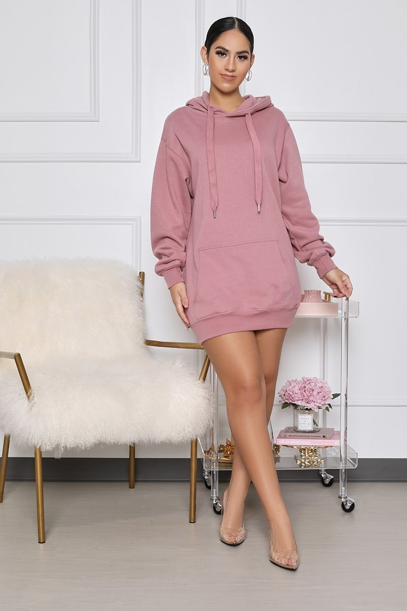 model wearing the mid-thigh length hoodie dress in pink
