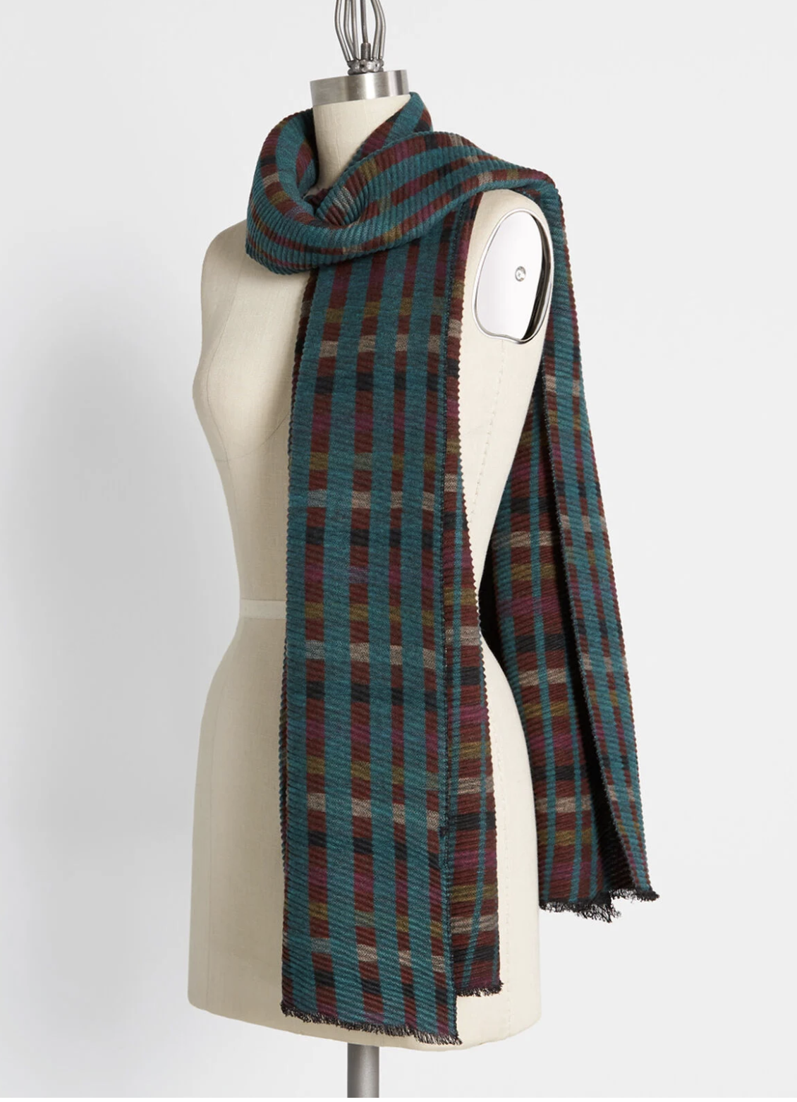 A long plaid scarf with dark green, purple, brown, and beige tones