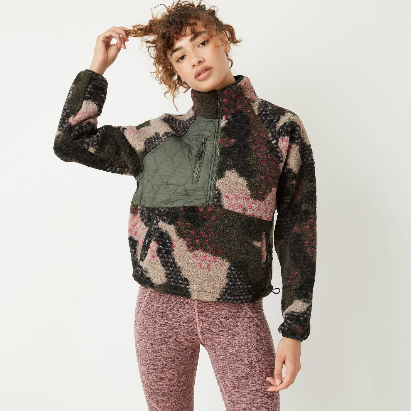 model wearing the quarter zip with green and tan camo print and pink dots and pockets on the sides and quilted green section with a pocket on the right chest