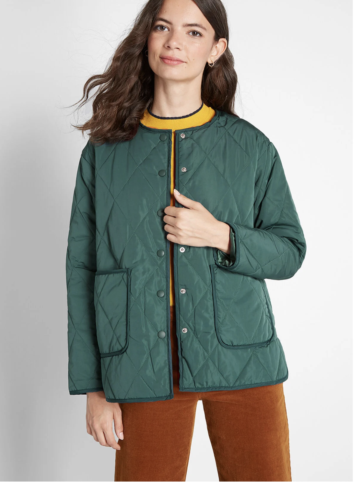 Model in green button up light puffer jacket with front pockets