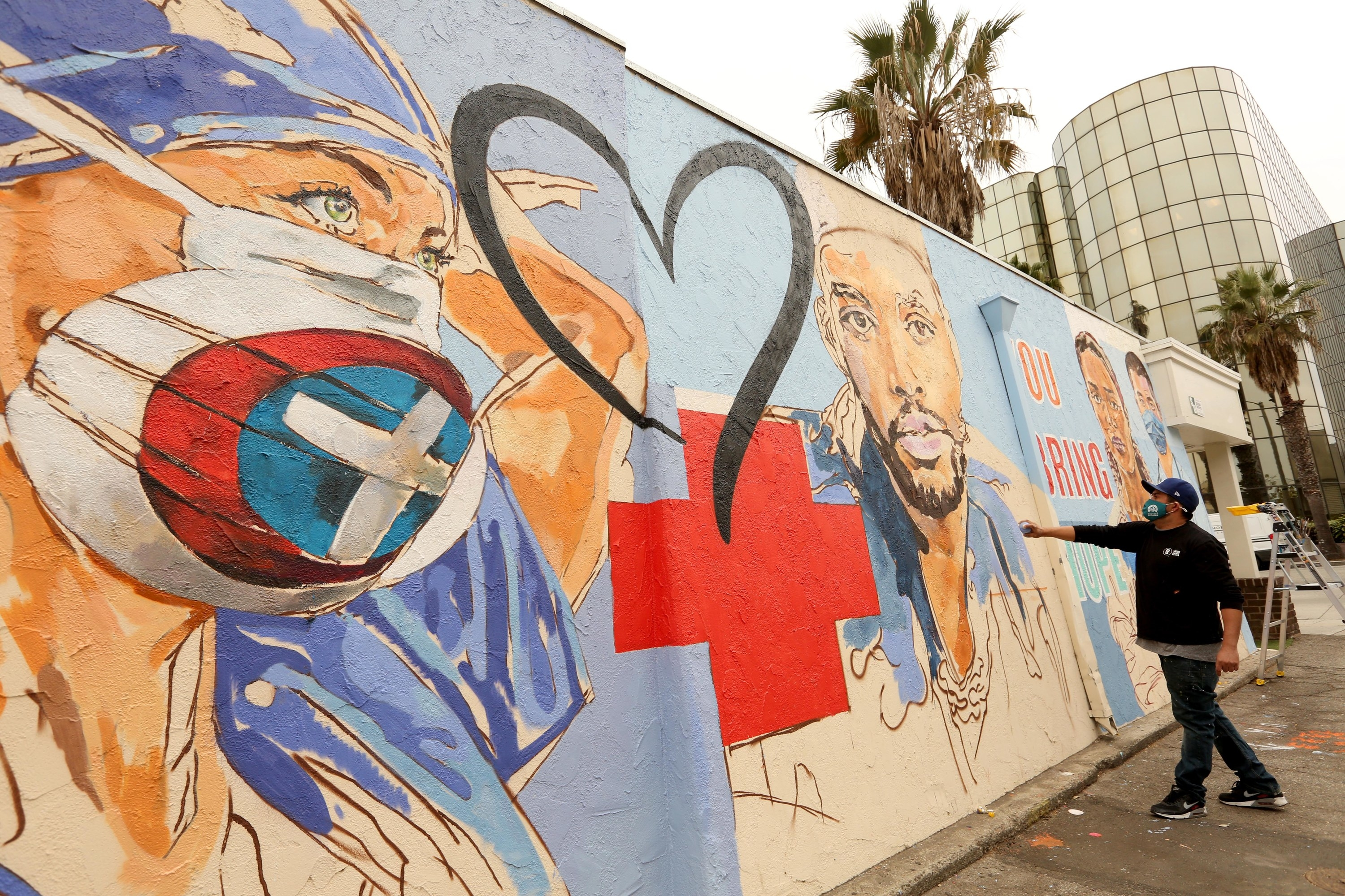 A street mural shows a red cross and heart between illustrations of healthcare workers
