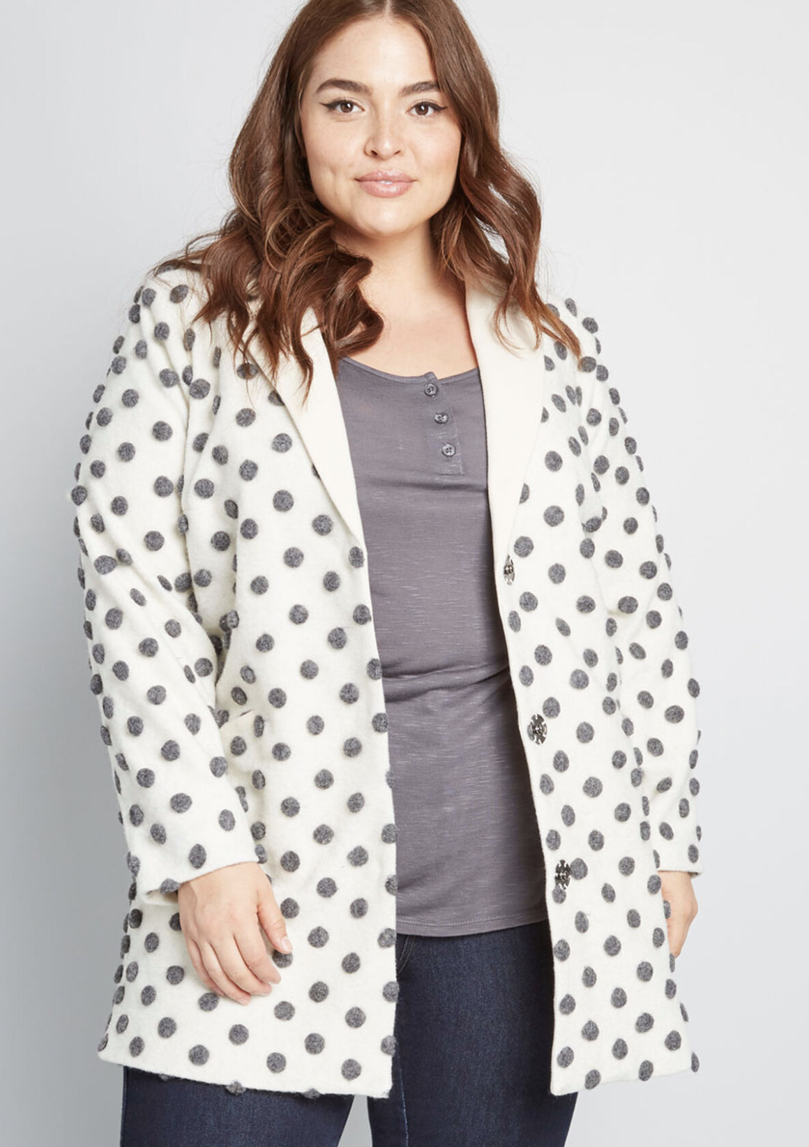 Model in ivory wool coat with gray pom-pom-esque pola dots