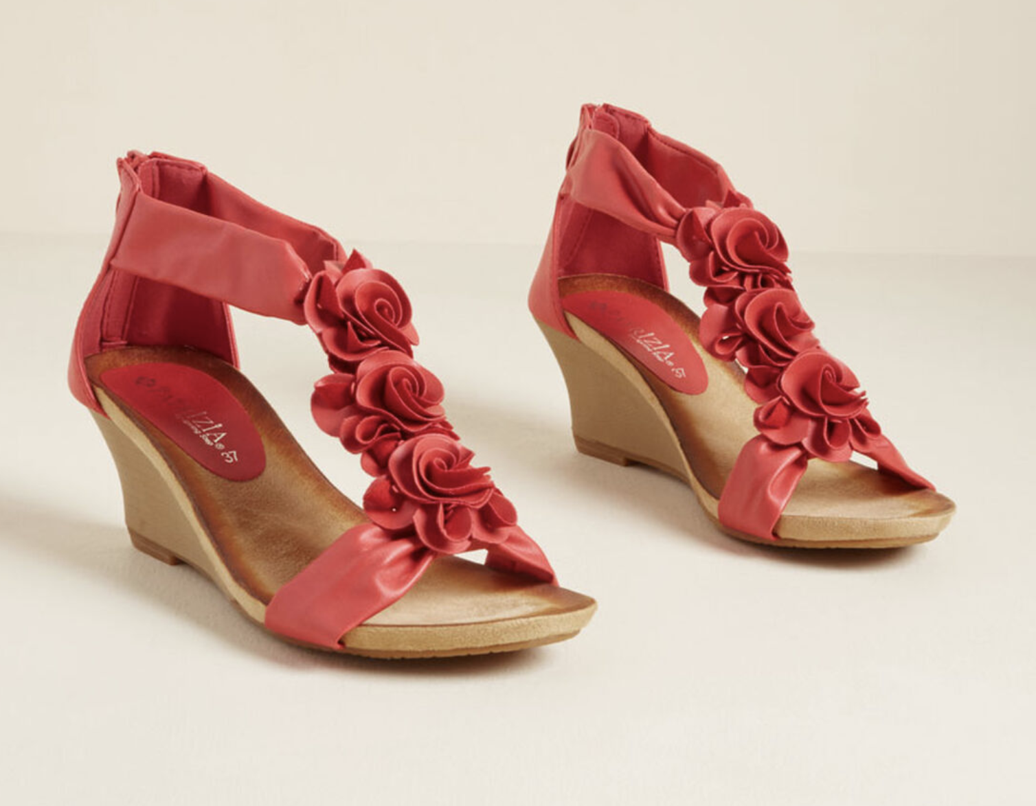 A pair of wedge heeled sandals with red rose detailing on the top of the foot