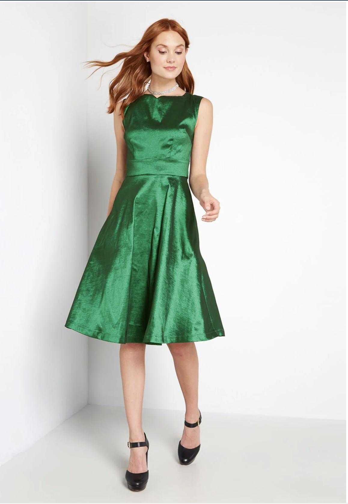 Model in sleeveless A-line green satin midi dress