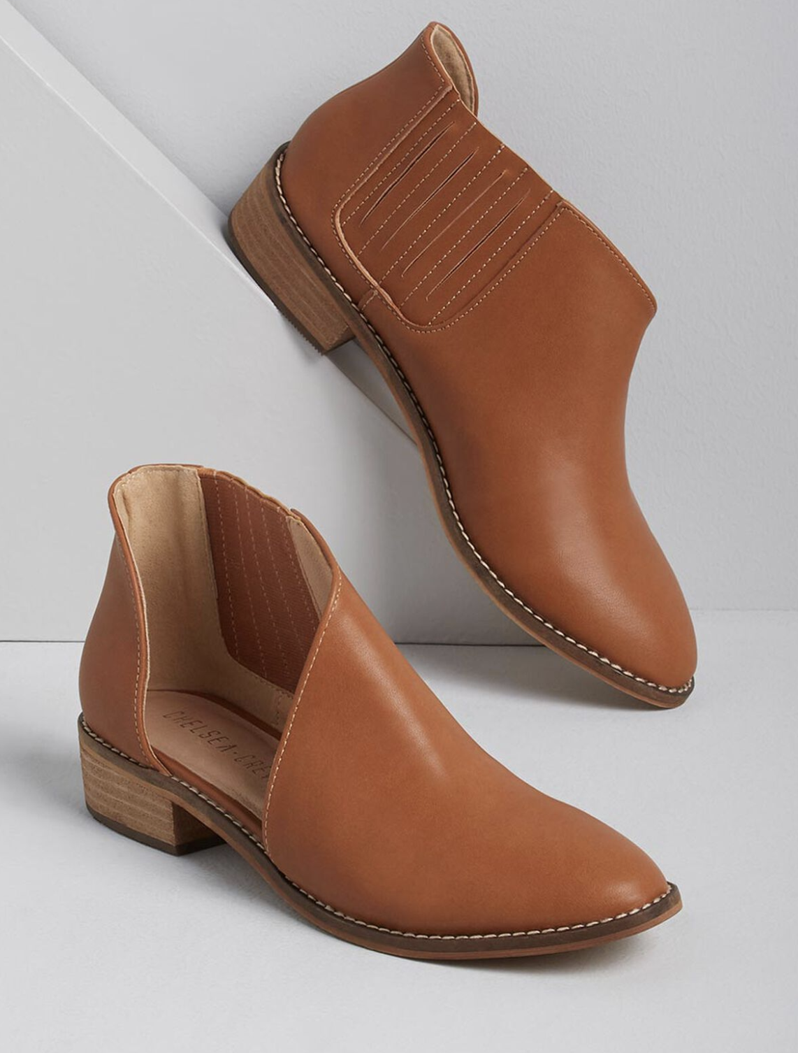 A pair of Chelsea ankle boots in light brown with a cut-out at the ankle