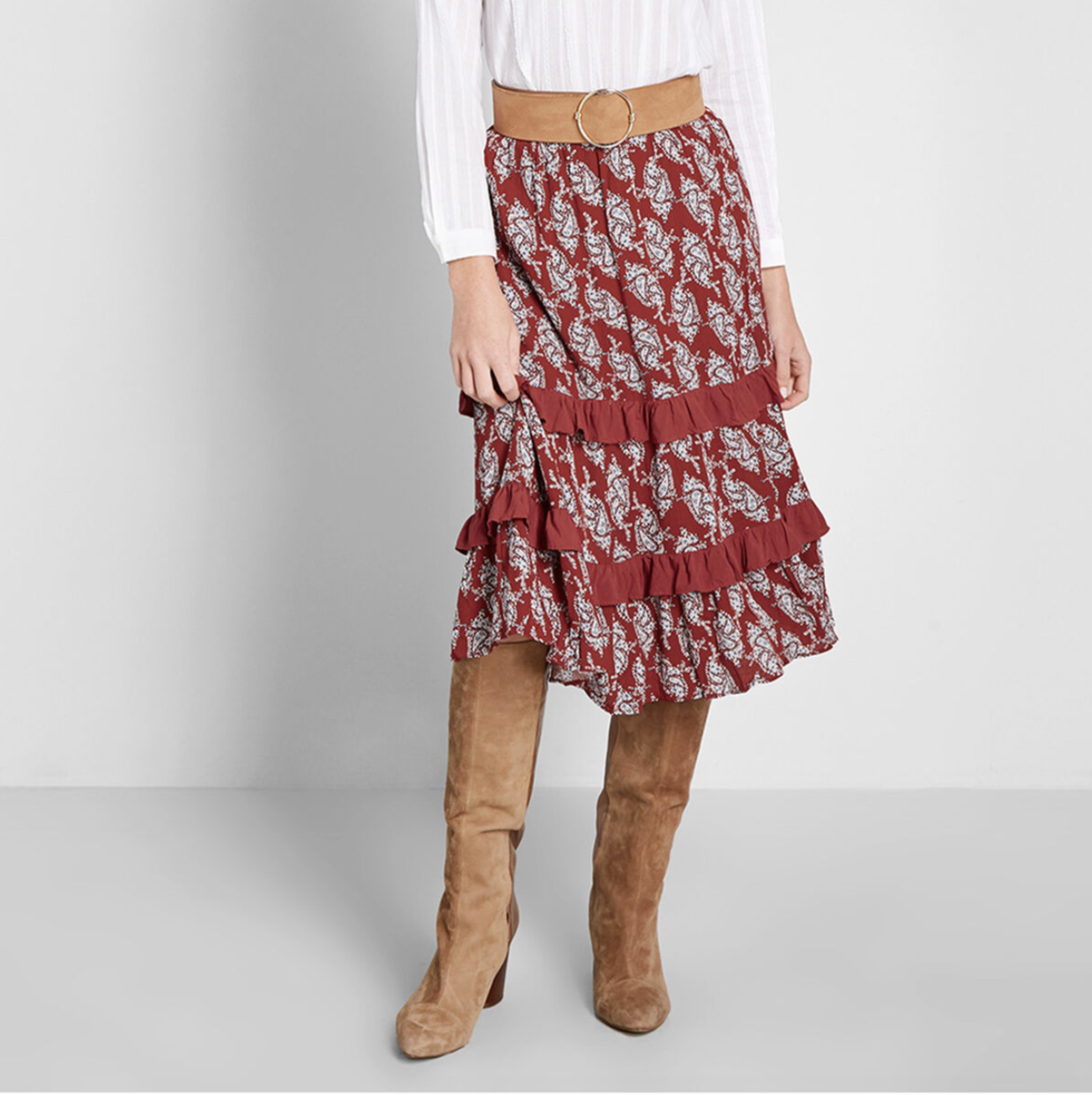 A model in a red tiered ruffled midi skirt with paisley print
