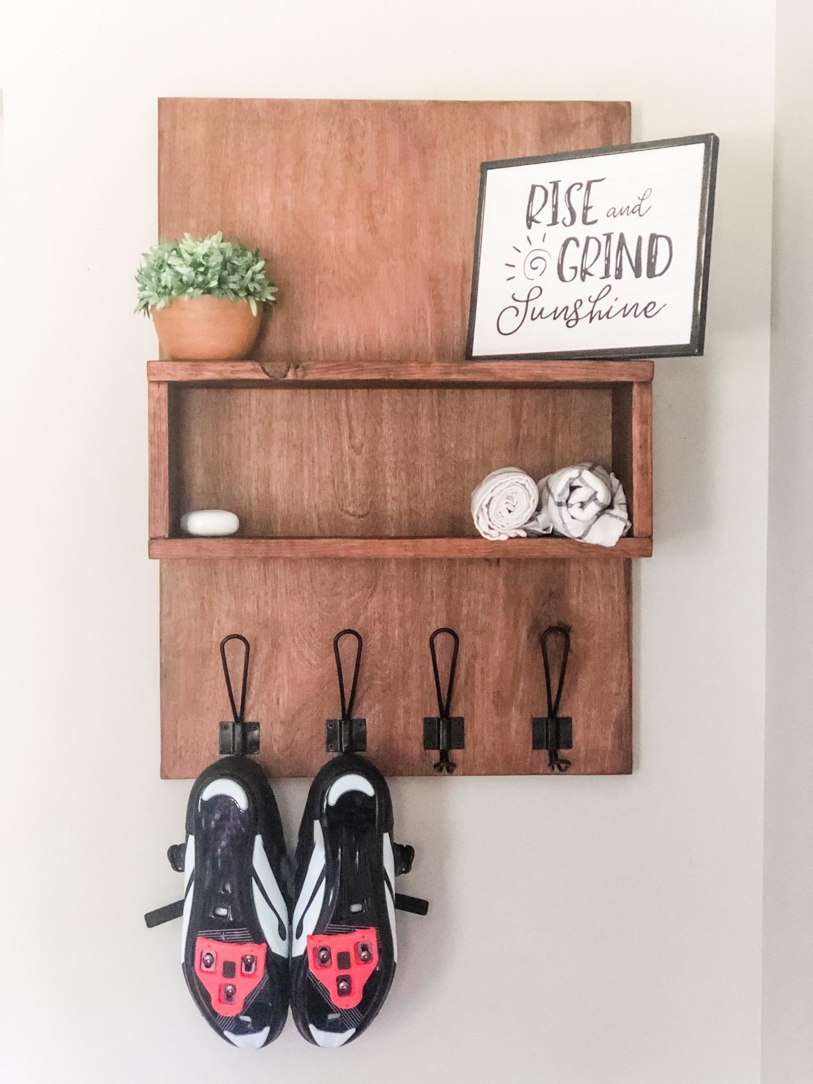 A wood shelf with hooks for the Peloton cleats hangs on the wall.
