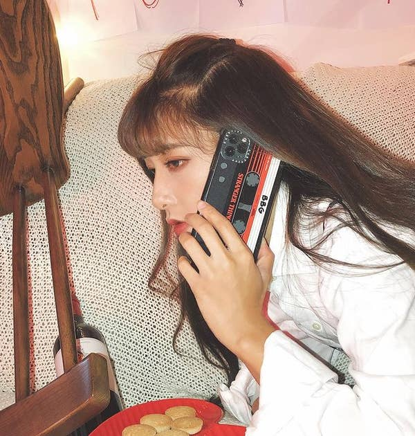 A woman holding her iPhone in a phone case that looks like a 1980s mixtape