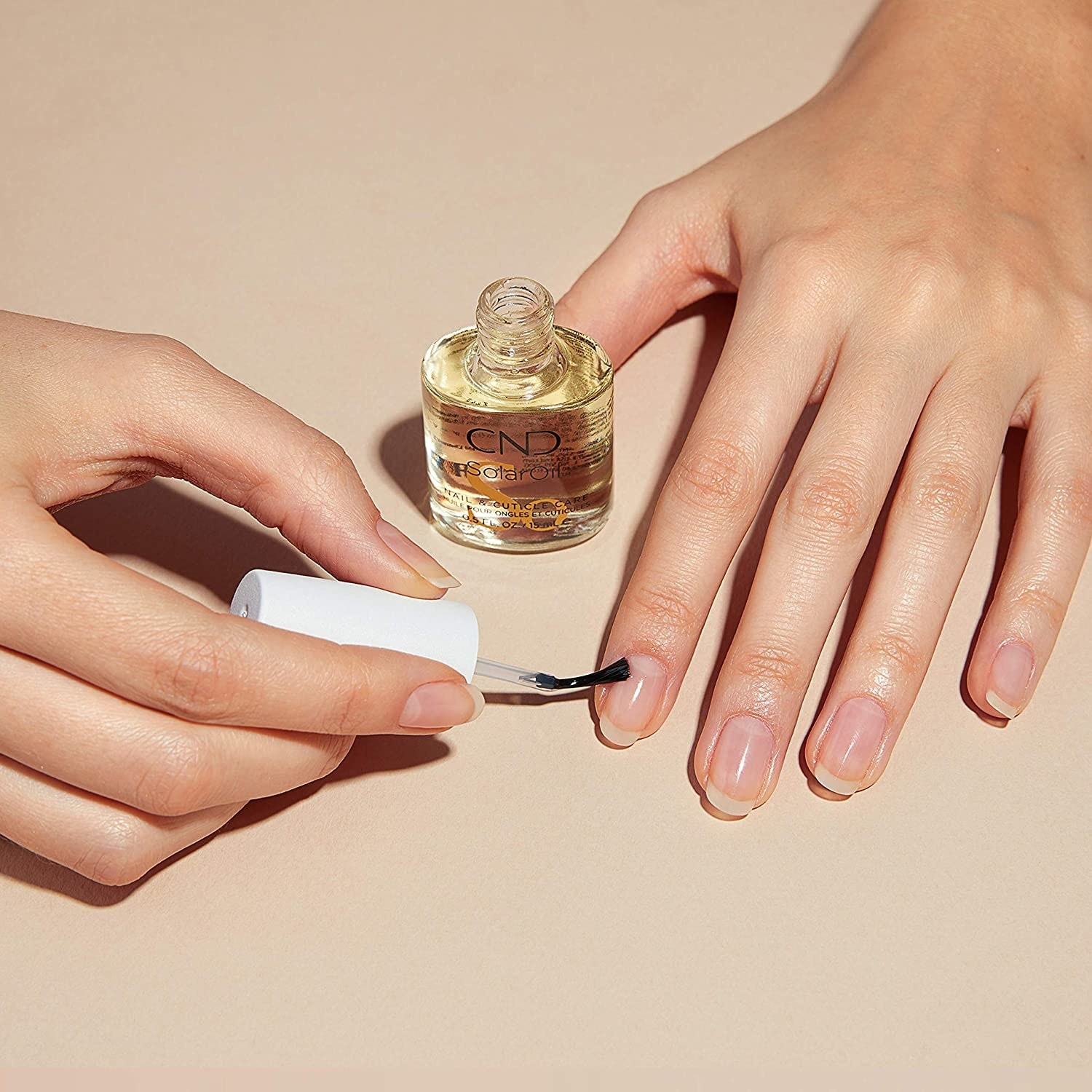 A person applying the cuticle oil to their nails