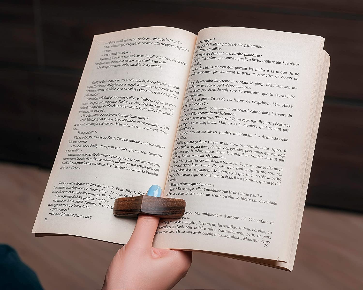 person using the book holder with one hand to open a book