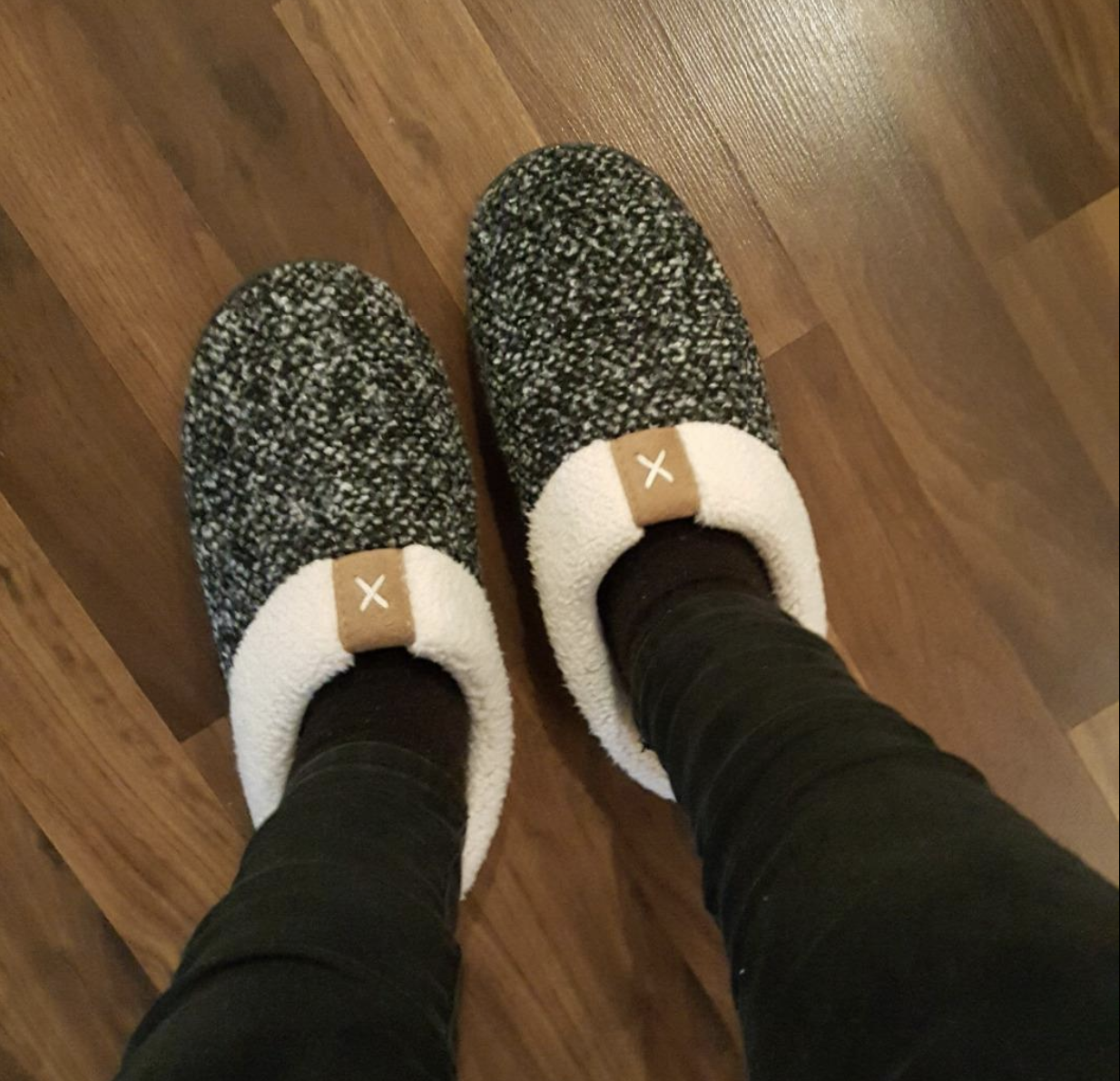 Reviewer in slip on white and black marled slippers with fleece-y lining