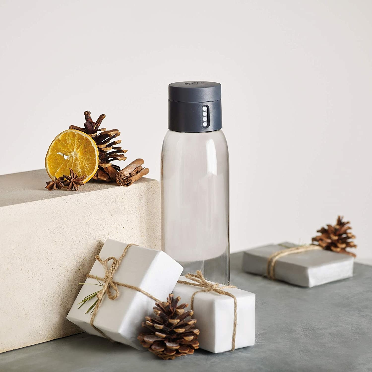 water bottle on a table surrounded by gift boxes and pine cones