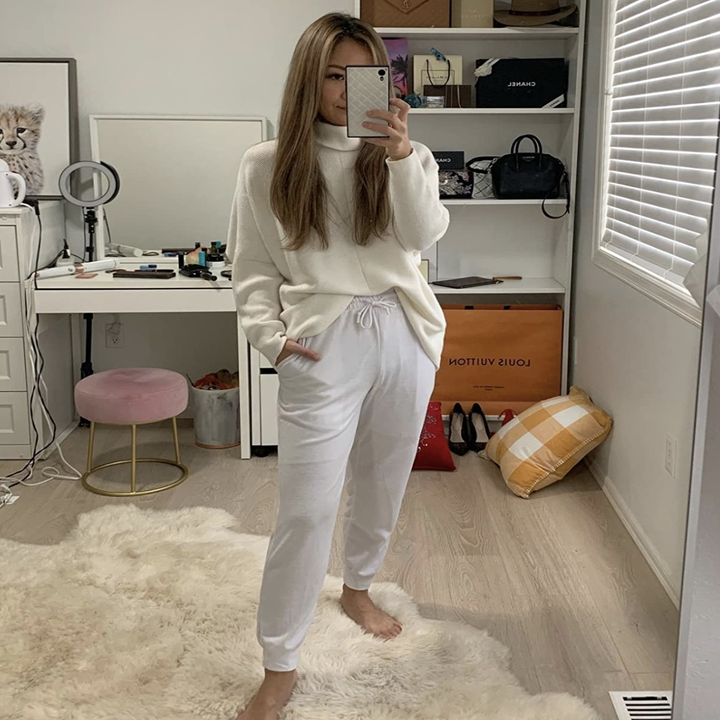 Reviewer in white oversized turtleneck sweater