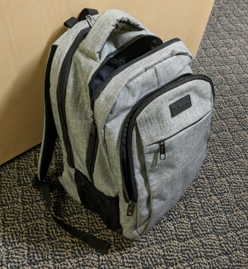 Reviewer image of gray backpack upright on floor showing multiple front pockets, laptop sleeve, and storage
